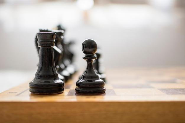チェスチップ、手前にポーンと黒い塔、ボード上、ゲームを開始する準備ができています。