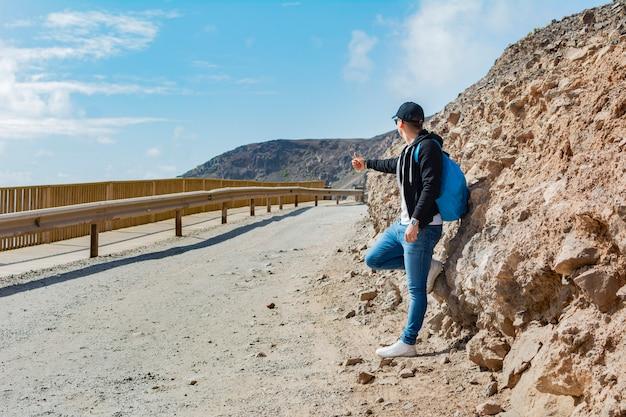 Авантюрист с синим рюкзаком путешествует автостопом по глухой и одинокой грунтовой дороге.