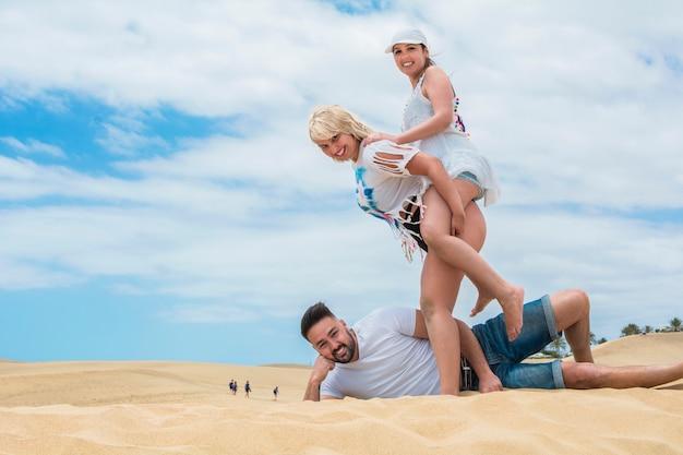 Трое друзей наслаждаются на пляже, на переднем плане, выглядят как гиганты перед группой людей, идущих по песчаным дюнам далеко.