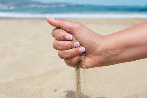 手がビーチで砂をこぼす
