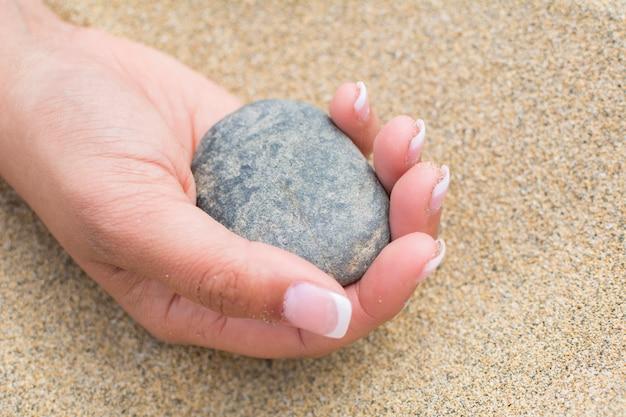 女性が小石を手に持っている