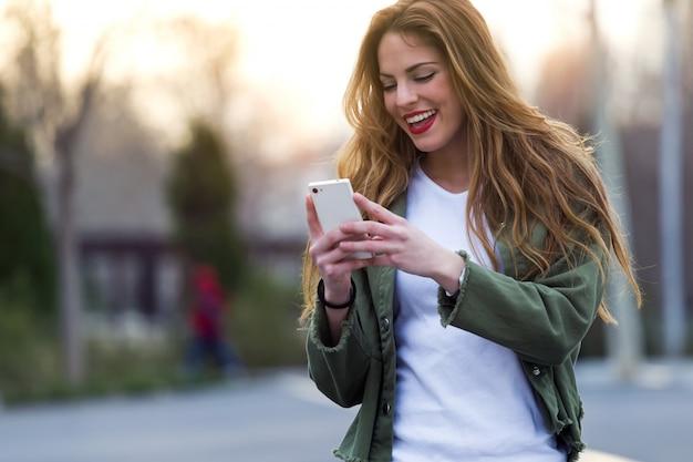 彼女の携帯電話を通りに使っている美しい若い女性。