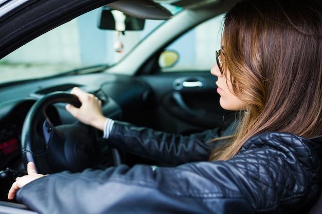 Красивая молодая женщина вождения ее автомобиль.