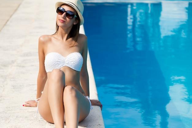Красивая, молодая, сексуальная девушка наслаждается летом возле бассейна.