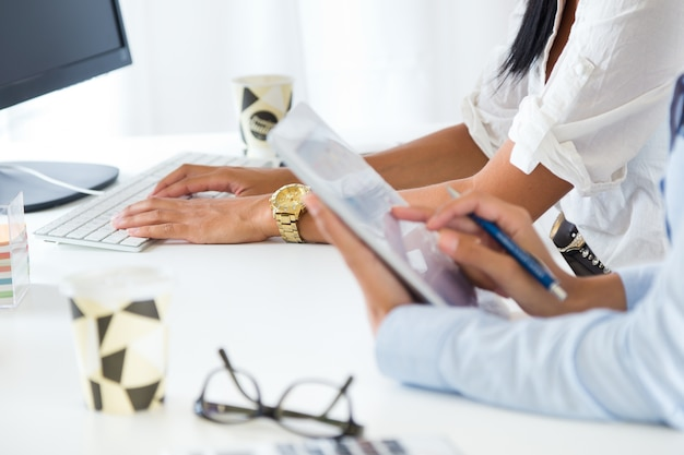 Два деловых женщин, работающих в офисе с цифровой таблетки.
