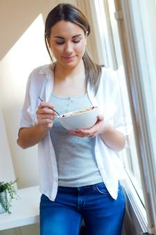 美しい若い女性が家庭で穀物を食べる。