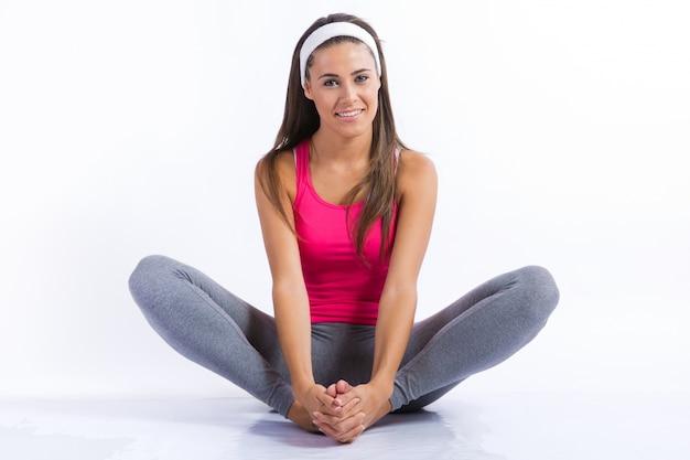 美しい健康的な若い女性は自宅で運動をしています。