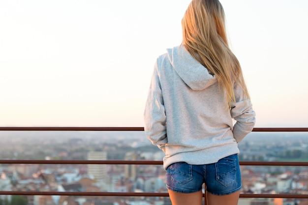 Красивая блондинка стоит на краю крыши.