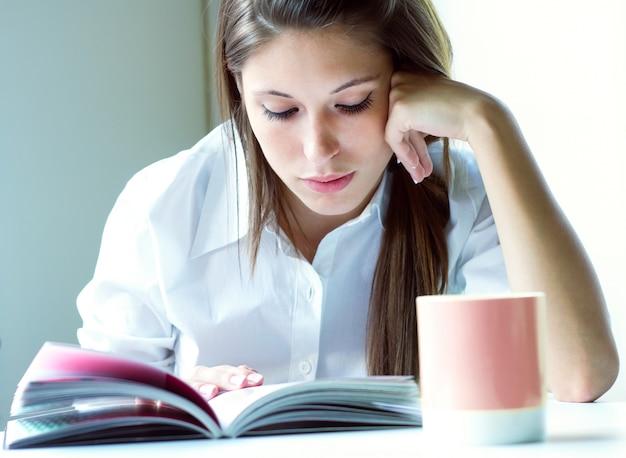 Портрет красивой молодой женщины, читая у себя дома