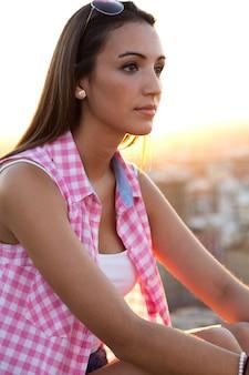 美しい女の子が日没の屋根に座っている。