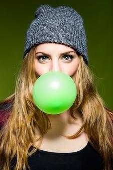 グリーンバブルガムを吹く美しい若い女性。隔離されています。