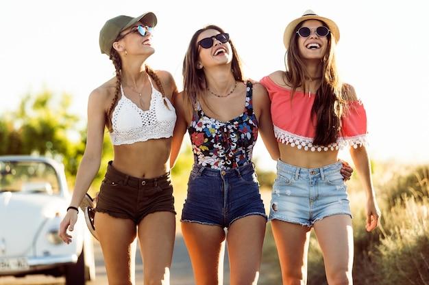 Молодые девушки смеялись с шортами и солнцезащитные очки