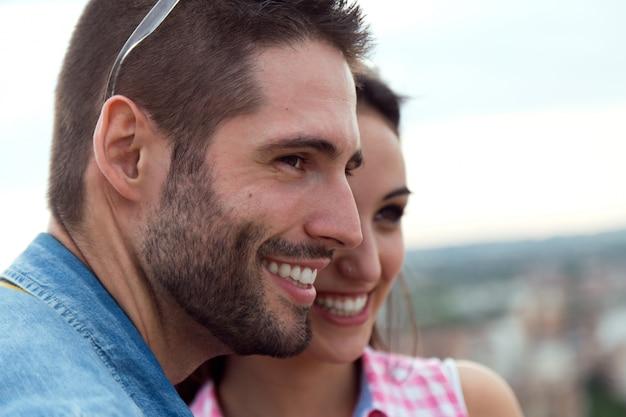 都市の景色を見ている若い観光客のカップル。