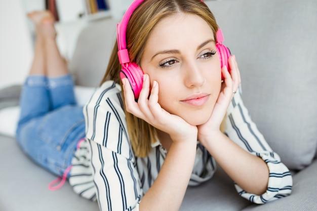 家庭で音楽を聴く美しい若い女性。