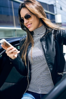 彼女の携帯電話を車で使っている美しい若い女性。