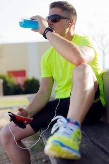 Красивый молодой человек, пить после бега.