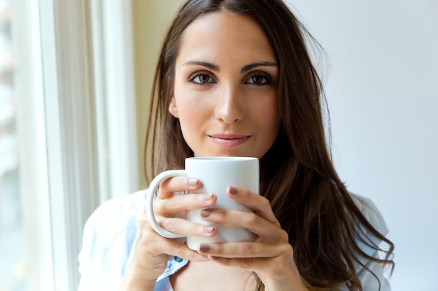 Красивая женщина пить кофе утром возле окна.
