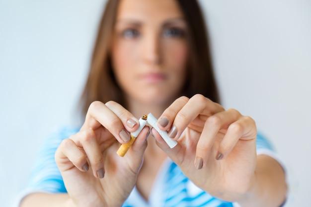 Молодая женщина отказывается курить и ломает сигарету.