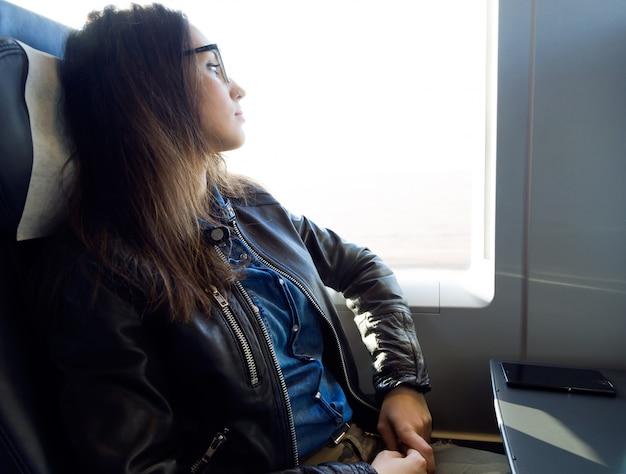Красивая молодая женщина, путешествуя на поезде.