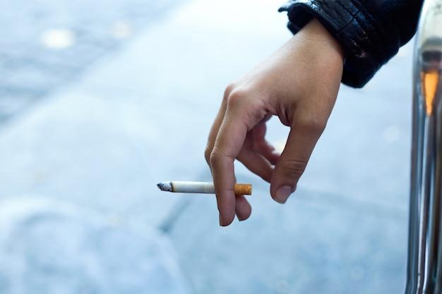 女の子は通りにタバコを持っています。