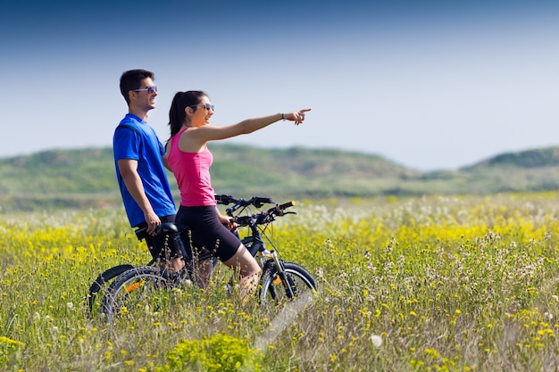 田舎の自転車に乗っている幸せな若いカップル