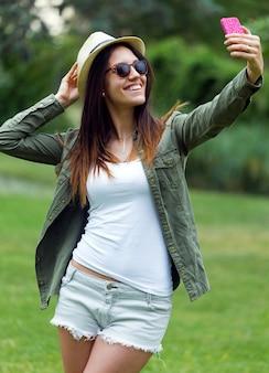彼女の携帯電話を公園で使っている美しい若い女性。