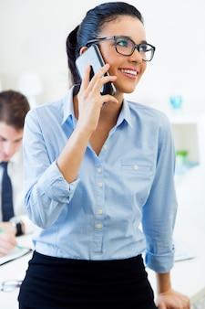 Деловые люди, работающие в офисе с мобильным телефоном.