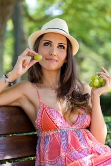 緑の葡萄を庭で食べる若い美しい女性。