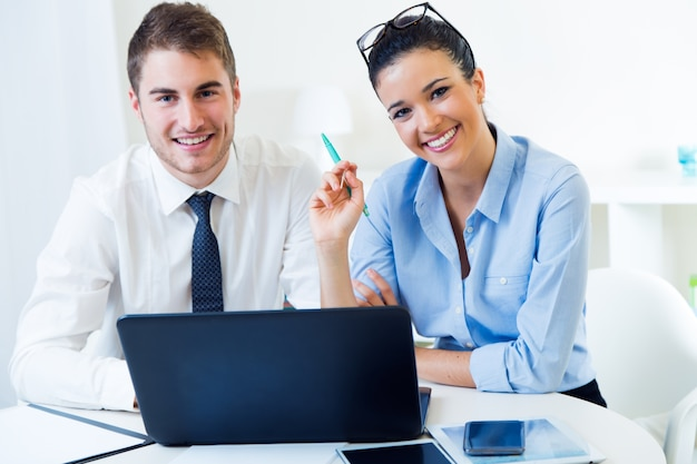 Деловые люди, работающие в офисе с ноутбуком.