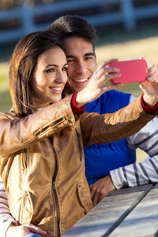 公園のスマートフォンで写真を撮っている若いカップル