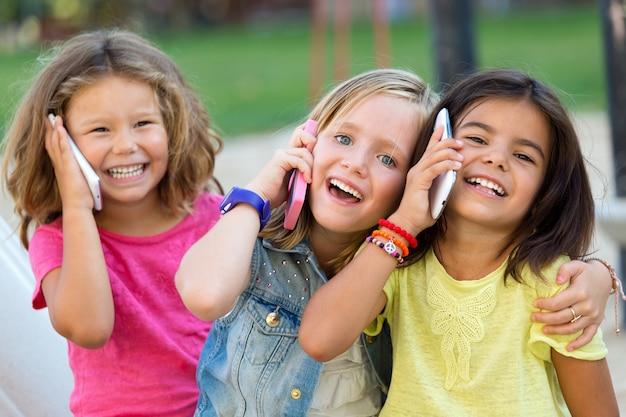 公園内の携帯電話を使用している子供のグループ。