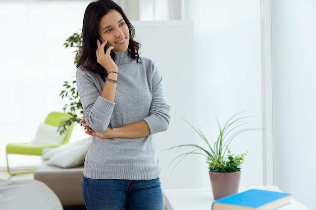 彼女の携帯電話を自宅で使っている美しい若い女性。