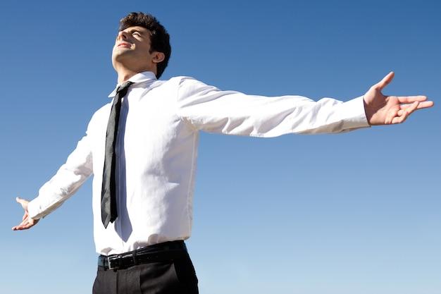 幸せな成功のビジネスマンは、空を背景に腕を上げた