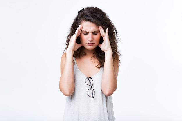 白い背景の上に頭痛を持つ美しい若い女性。