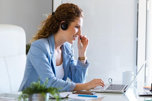 Оператор обслуживания клиентов разговаривает по телефону в офисе.