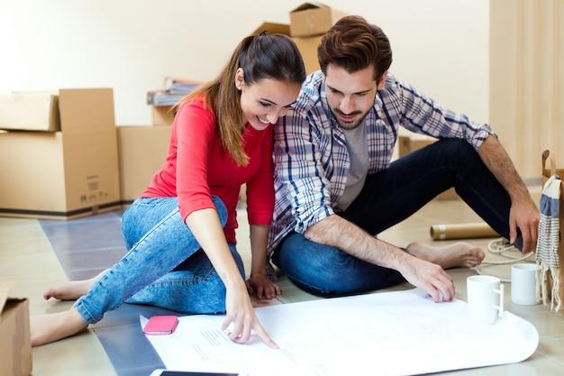 彼らの新しい家の青写真を見ている若いカップル