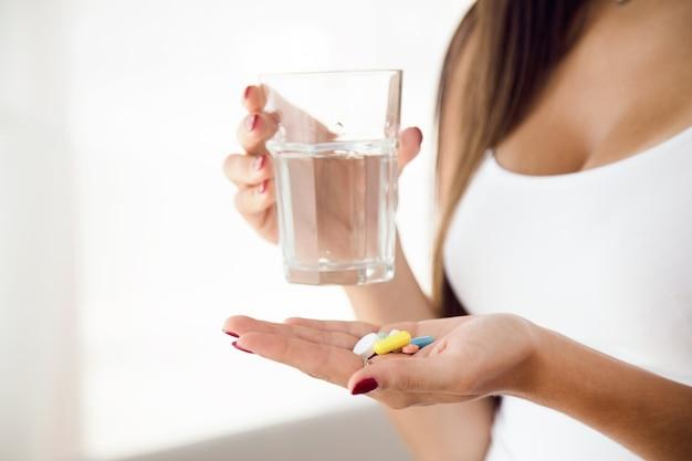 Молодая женщина, принимая таблетки у себя дома.