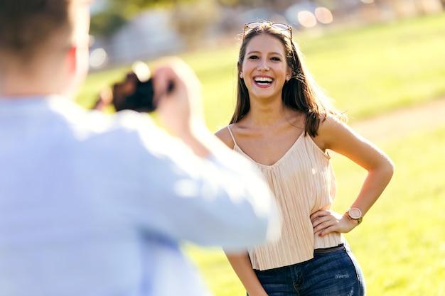 公園で彼のガールフレンドの写真を撮っているハンサムな若い男。
