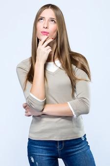 白い背景を考えている美しい若い女性。