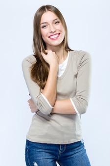 Красивая молодая женщина, глядя на камеру на белом фоне.
