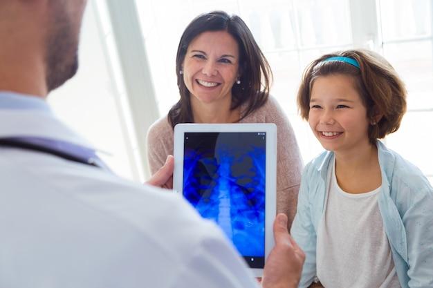 Мужской врач консультирует рентгенографию грудной клетки девушки в офисе.