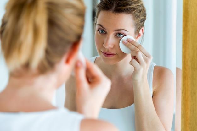 Красивая молодая женщина чистит ее лицо, глядя в зеркало в ванной комнате.