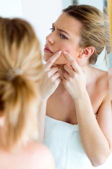 Красивая молодая женщина, удаление прыщ с ее лица в ванной комнате дома.