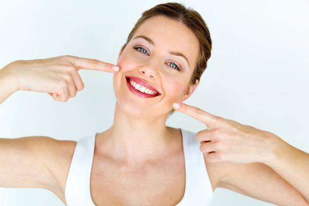 完璧な笑顔で美しい若い女性。白で隔離されています。