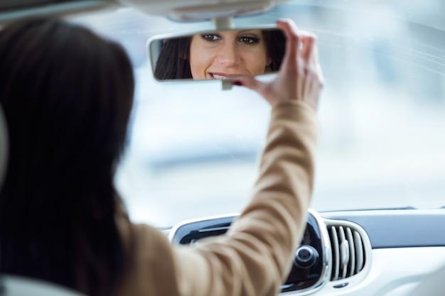 車の後部鏡を固定している美しい若い女性。