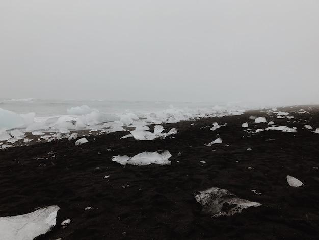 Укладка льда на черном песчаном пляже