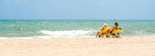 Вид сзади молодая счастливая пара геев, сидя на пляже