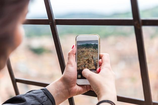 塔の上から携帯電話で都市の写真を撮る