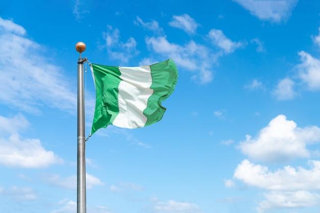 背景の青い空にナイジェリアの旗