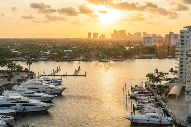 フォートローダーデールで太陽が沈む運河に豪華ヨットが停まっています。マリーナエリアでの夕日とフォートローダーデール港